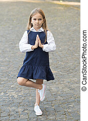 Meditate to develop mental muscles. Little child in uniform meditate outdoors. Small kid balance on leg with praying hands. Back to school. Mindful education. Meditation for beginners