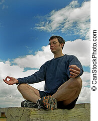 Meditate to the sky - Man meditates outside on a bench