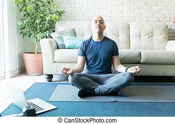 Meditating and doing yoga at home