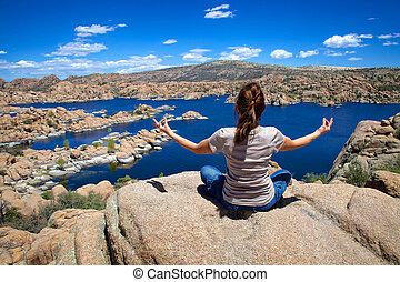 Meditating at Watson lake - a woman meditating on one of the...