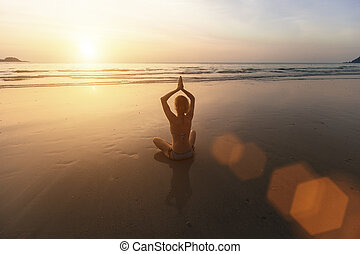 meditating in yoga pose at sunset