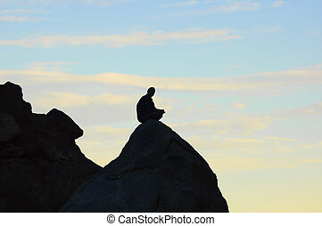 Meditating man sitting on top of a rock in the mountains