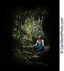 meditating - Yong cross-legged woman relaxing on the jungle...