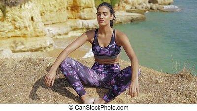 Meditating sportswoman on ocean coast