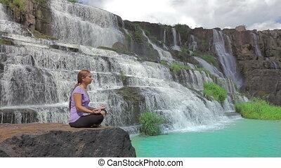 Meditating - Young woman meditating at the waterfall