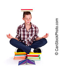 Meditating teenager - Teenage schoolboy sitting on books,...