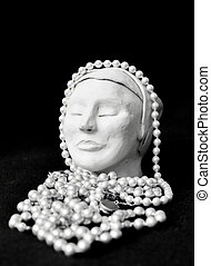 Meditating with pearls. Sculpture of female head with ...
