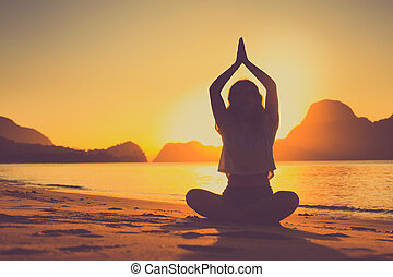 meditating woman by the ocean with rocks in the background at sunset