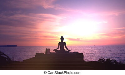 Silhouette of a woman meditating against a sunset in the ocean.