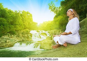 Meditation at sunrise time - Young woman meditating at...