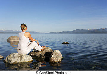 Meditation - Attractive woman in white meditating by still ...