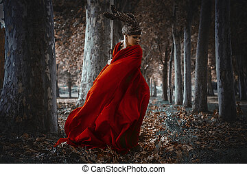 meditation, blonde girl with a huge red cloth in the wind, warrior and freedom, forest brown leaves in autumn