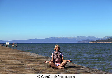 Meditation girl yoga on the beach on Tahoe, California