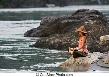 Meditation near Ganga - Young woman meditates sittink on the...