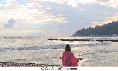 Meditation near the sea and doing yoga on a beach at sunrise