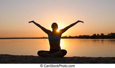 Meditation near the sea and doing yoga on a beach at sunset