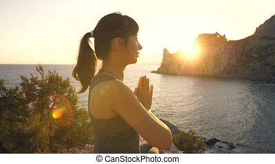 Meditation of young woman at sunset