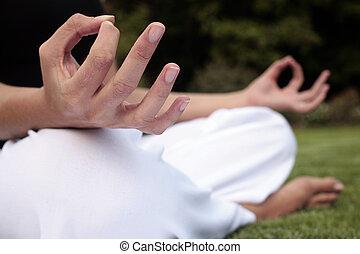 Meditation on a Lawn - Woman sitting down meditating on a...
