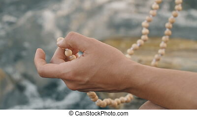 Meditation on the beads - Man meditating with beads near the...