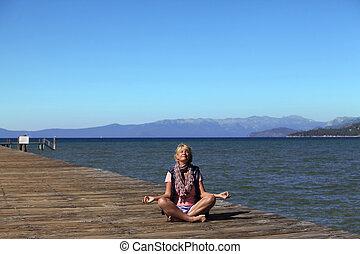 Meditation girl yoga on the beach on Tahoe, California