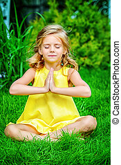 meditation - Pretty little girl sitting on a green lawn in...