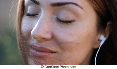 Meditation. Relax. Woman closeup in headphones smiling and listening music with her eyes closed outdoor