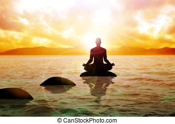 Meditation - Silhouette of a man figure meditating on calm...