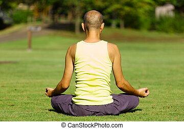 meditation - man sitting on a lawn and meditating calmly...