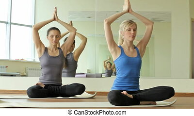 Meditation - Yoga girls sitting in a lotus pose, exhaling...