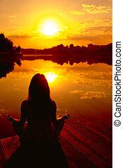 Meditation - Woman doing yoga at sunset