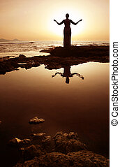 Meditation - Woman in meditation pose at sunset with ...