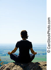 Meditation - Woman on the top of a mountain meditating
