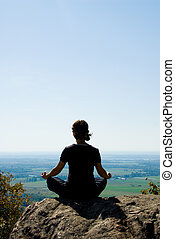 Meditation - Woman on the top of a mountain relaxing