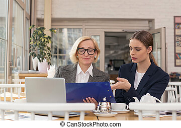 Meditative businesswoman discussing statistics with her apprentice