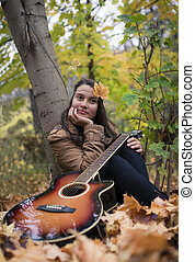 Meditative girl with a guitar in autumn
