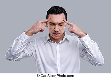 Meditative man touching his temples while thinking