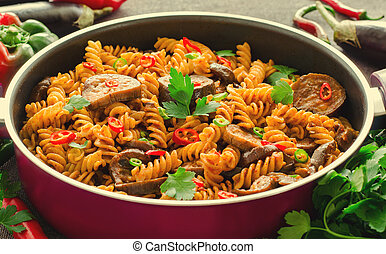 Mediterranean eggplant pasta in pot with tomatoes, pepper and parsley on grey background.