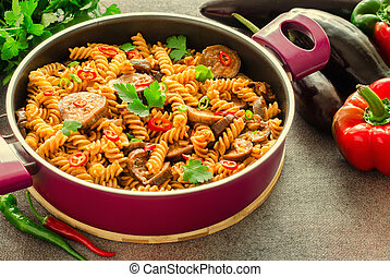 Mediterranean eggplant pasta in pot with tomatoes, red pepper and parsley on grey background.