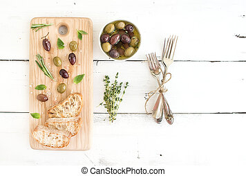 Mediterranean olives with herbs and ciabatta slices on rustic wooden board over white background, top view