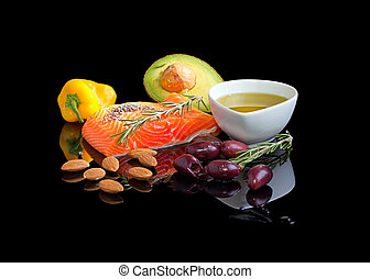 Mediterranean omega-3 diet. Fish steak, olives, nuts and herbs isolated on black background with reflection.