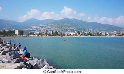 Mediterranean sea shore with fishermen in Alanya, Turkey