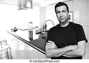Medium age man in modern kitchen interior portrait