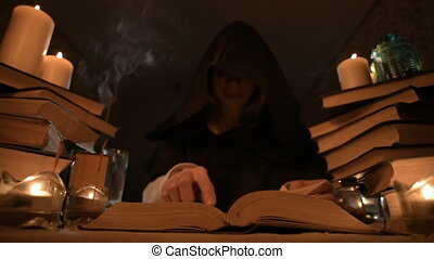 Medium close-up girl magician in a hood in a dark room by...