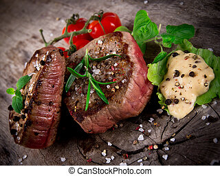 Medium grilled bbq steaks with fresh herbs and tomatoes