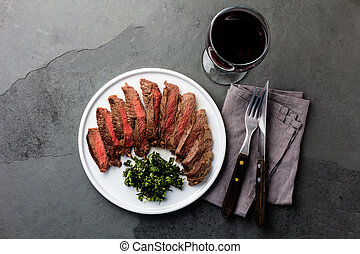 Medium rare beef steak on white plate, glass of red wine