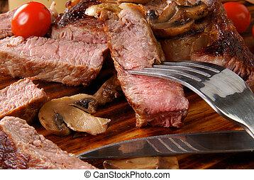 Medium rare rib steak broiled with mushrooms and tomatoes