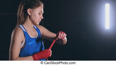 Medium shot A beautiful female boxer pulls red bandages onto...