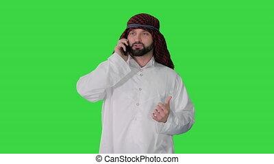 Arab sheikh making a call walking on a Green Screen, Chroma Key.