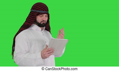 Medium shot. Arabic business man with tablet on a Green Screen, Chroma Key. Professional shot in 4K resolution. 044. You can use it e.g. in your medical, commercial video, business, presentation, broadcast