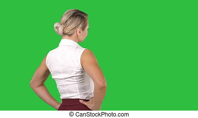 Business woman placing hands on hips on a Green Screen,...